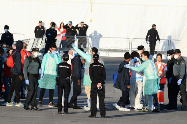 Red Cross members, Spanish Guardia Civil guards and Spanish policemen welcome migrants from the Italian...