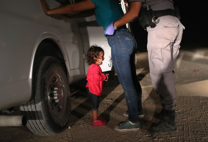 A two-year-old Honduran asylum seeker cries as her mother is searched and detained near the U.S.-Mexico border earlier this m