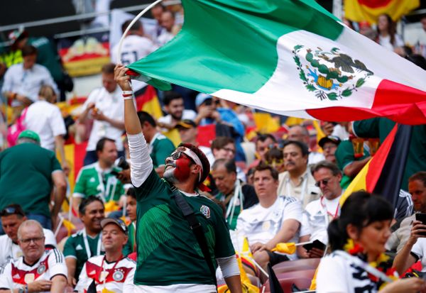 Mexico fan waves a flag inside the stadium before the match.