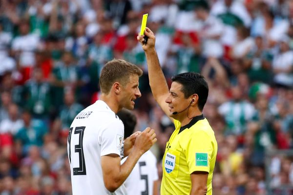 Germany's Thomas Muller is shown a yellow card by referee Alireza Faghani.