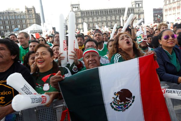 Mexican fans react while watching the broadcast at the Zocalo square.
