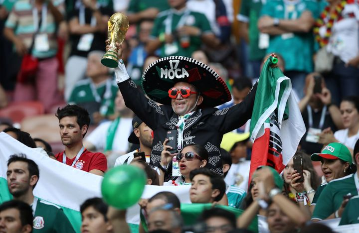 Mexico fan holds a replica World Cup trophy inside the stadium before the match.