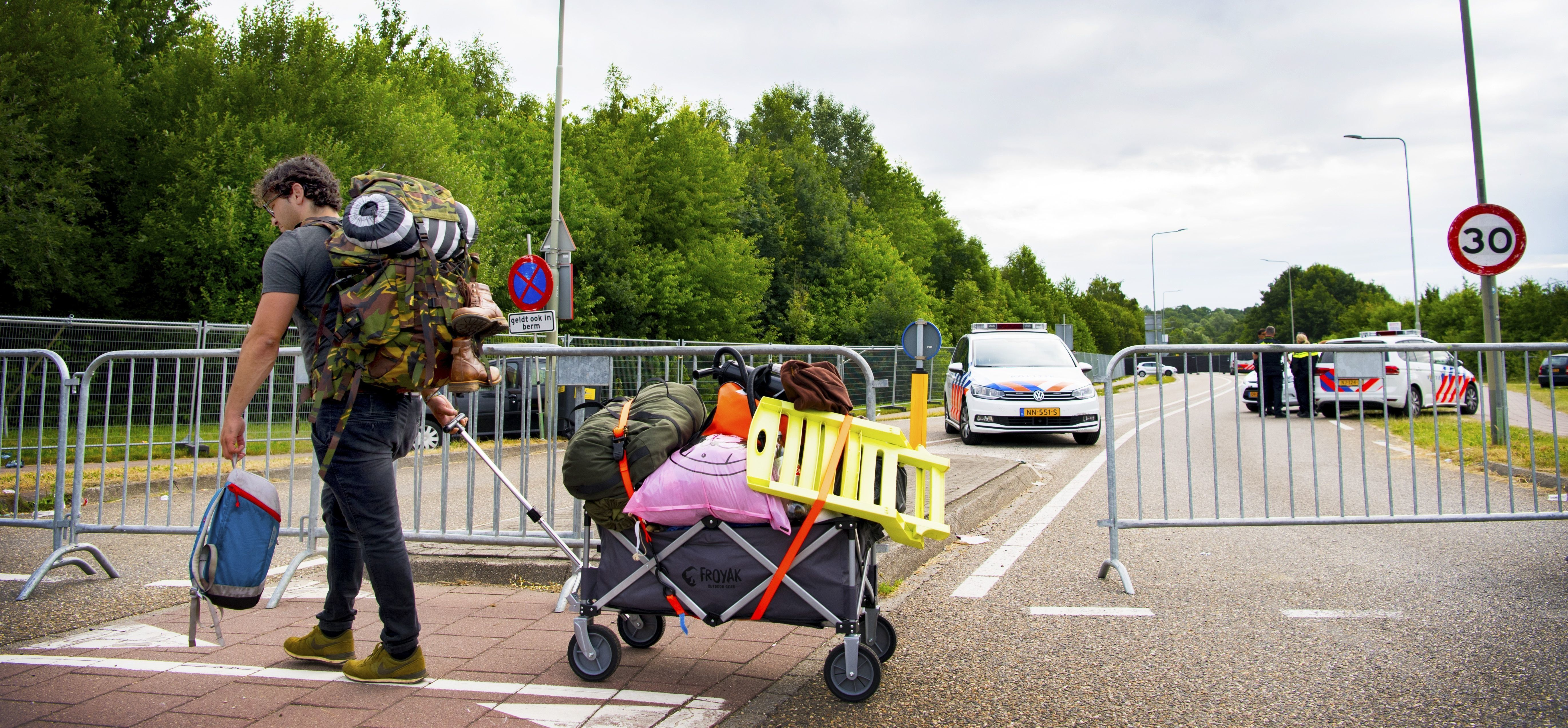 A man carries a trolley with bags past police cars near the site of the Pinkpop festival in Landgraaf, on June 18 2018, after a van slammed into pedestrians, killing one and injuring three. - The four pedestrians were hit around 4:00 am (0200 GMT) on June 18, 2018 by the van which then fled the scene, only hours after the end of the three-day Pinkpop Festival in the southern town of Landgraaf, near the German border. (Photo by Piroschka van de Wouw / ANP / AFP) / Netherlands OUT        (Photo credit should read PIROSCHKA VAN DE WOUW/AFP/Getty Images)