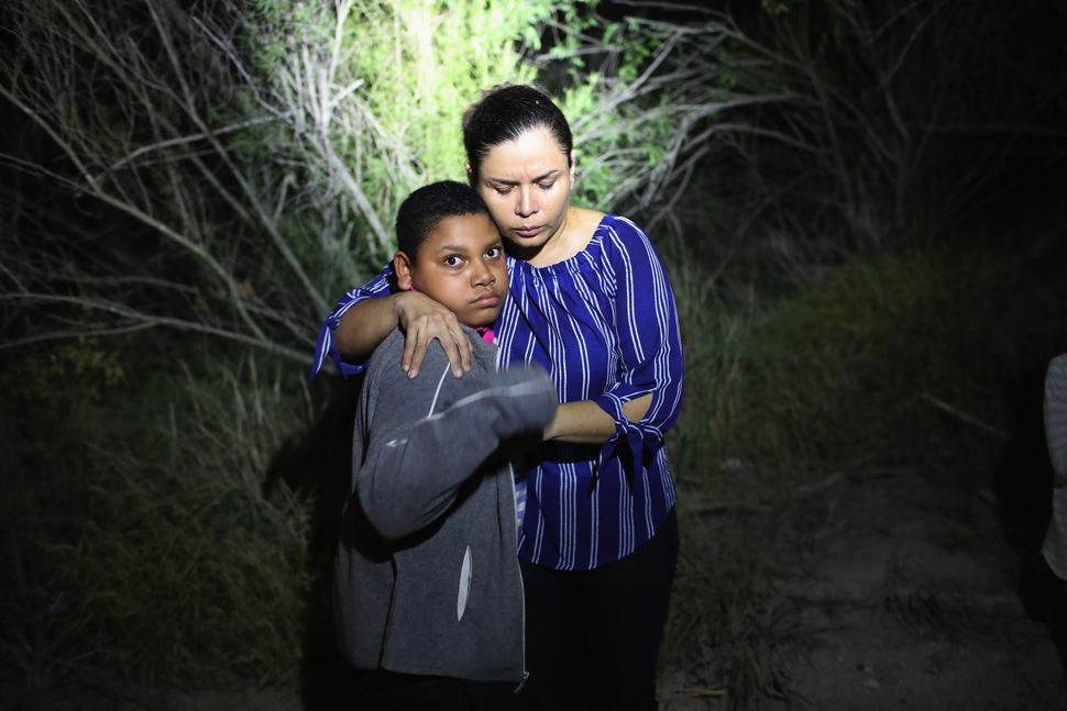 A U.S. Border Patrol spotlight shines on a terrified mother and son from Honduras as they are found in the dark near the U.S.