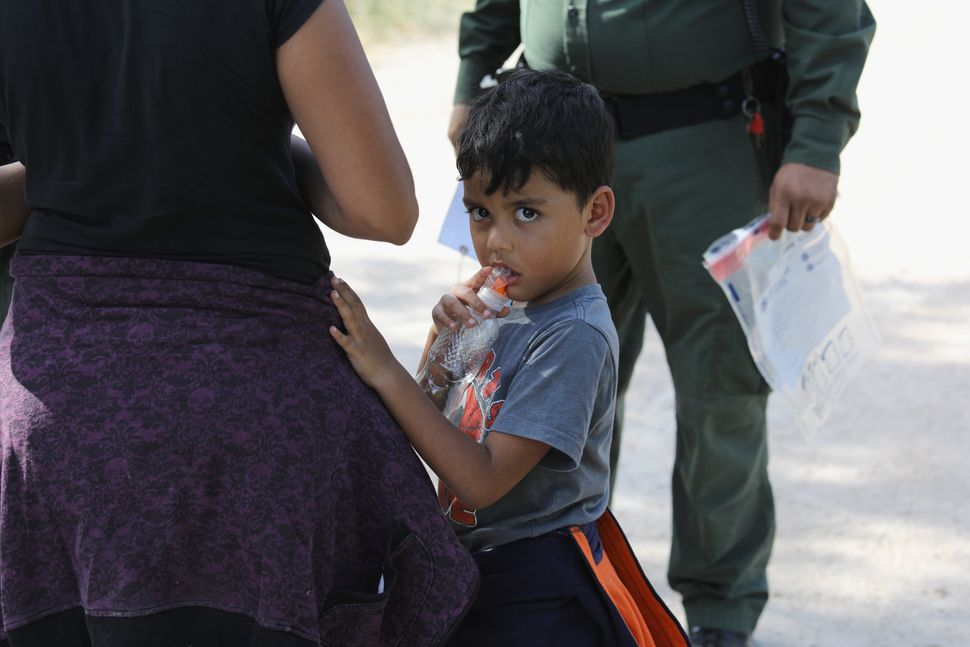 Central American asylum seekers wait as they are taken into custody on June 12, 2018.