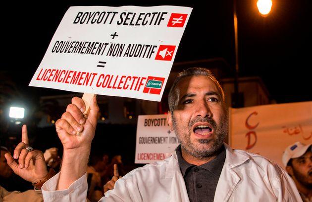 Un manifestant tient une pancarte pendant le sit-in des employés de Centrale Danone contre le...