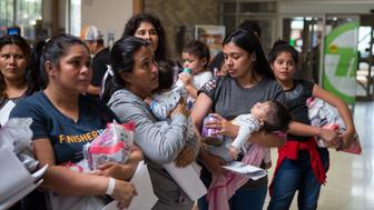 Immigrants wait to head to a nearby Catholic Charities relief center after being dropped off at a bus station shortly after release from detention through 'catch and release' immigration policy on June 17, 2018 in McAllen, Texas. - 'Catch and release' is a protocol under which people detained by US authorities as unlawful immigrants can be released while they wait for a hearing. (Photo by Loren ELLIOTT / AFP)        (Photo credit should read LOREN ELLIOTT/AFP/Getty Images)
