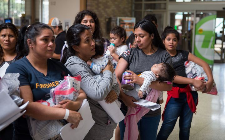 Immigrants wait to head to a nearby Catholic Charities relief center after being dropped off at a bus station shortly after r