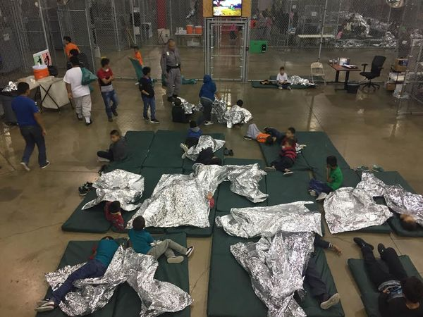 Migrant children sleep in what looks like a fenced-in area. The cage-like structures open up to common areas with portable re