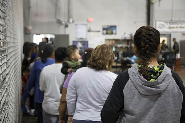 People wait in line outside one of the cages.