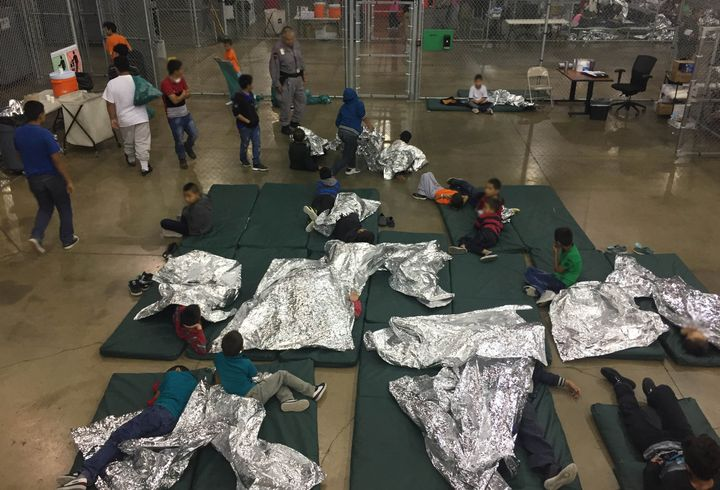 Children lie on sleeping pads with space blankets at the Rio Grande Valley Centralized Processing Center in Rio Grande City,