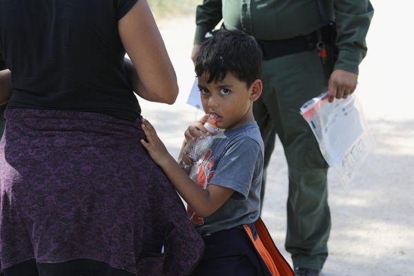 Central Americans seeking asylum wait as U.S. Border Patrol agents take them into custody on June 12, 2018, near McAllen, Tex
