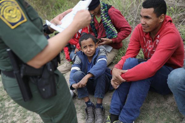 A U.S. Border Patrol agent checks birth certificates while taking Central American immigrants into detention on Jan. 4, 2017,