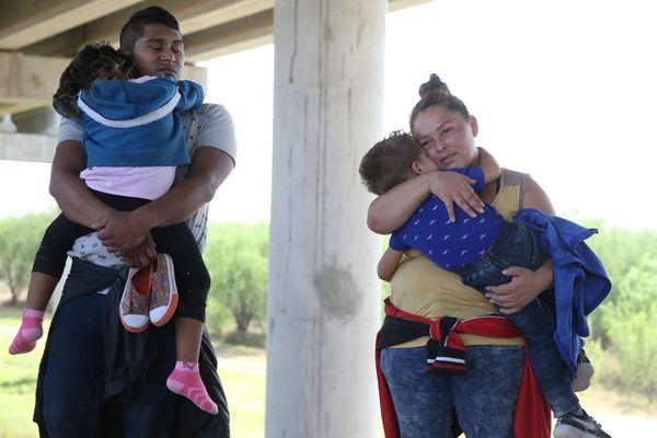 Adults and children await processing near McAllen, Texas, on April 2, 2018.