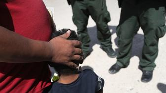 MISSION, TX - JUNE 12:  U.S. Border Patrol agents take a father and son from Honduras into custody near the U.S.-Mexico border on June 12, 2018 near Mission, Texas. The asylum seekers were then sent to a U.S. Customs and Border Protection (CBP) processing center for possible separation. U.S. border authorities are executing the Trump administration's zero tolerance policy towards undocumented immigrants. U.S. Attorney General Jeff Sessions also said that domestic and gang violence in immigrants' country of origin would no longer qualify them for political-asylum status.  (Photo by John Moore/Getty Images)