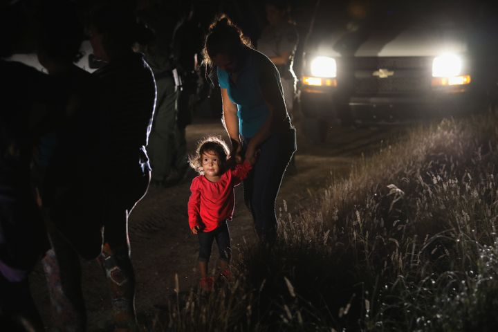 A 2-year-old Honduran stands with her mother after being detained by U.S. Border Patrol agents near the U.S.-Mexico border on