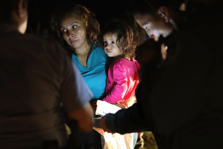 A Honduran mother holds her 2-year-old as U.S. Border Patrol agents review their papers near the U.S.-Mexico border on June 1