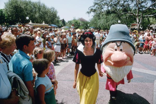 A crowd gathers to watch Snow White and Grumpy at Disneyland in 1969.