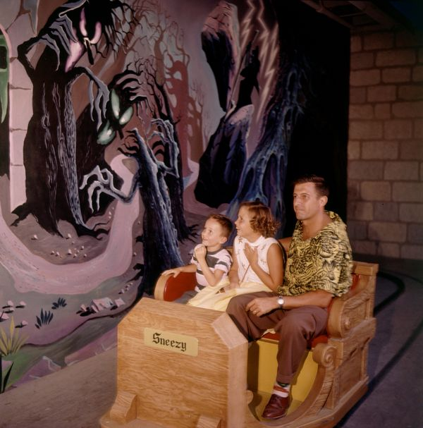 A man and two children move past a scary illustration on the Snow White ride at Disneyland in 1955.