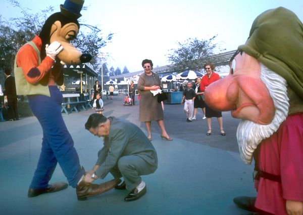 A Disneyland guest ties Goofy's shoes during a visit in 1962.