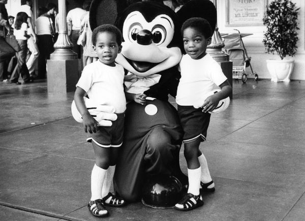 Two children pose with Mickey Mouse at Disneyland in 1982.