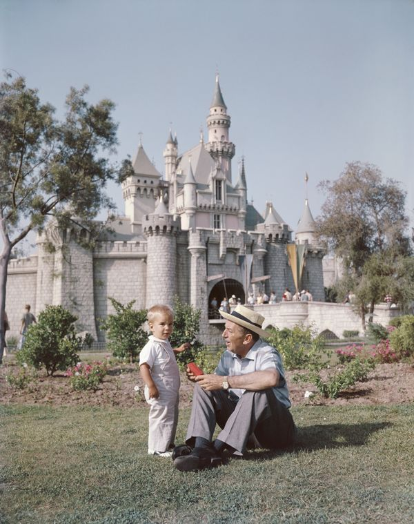 Disney with one of his grandsons on the lawn outside Sleeping Beauty Castle shortly after Disneyland's opening.
