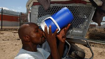 Desmont Smith, who is homeless, sit in the shade of his shopping cart drinking water, near the train tracks in Phoenix where the temperature reached 108 degrees. Water was passed out by volunteers to the homeless who were believed to make up more than half of the 20 heat related deaths this week. The Western USA broke records with the temperature in Phoenix reaching 117 degrees, 117 in Las Vegas and 129 recorded in Death Valley in the last ten days. (Photo by Ann Johansson/Corbis via Getty Images)