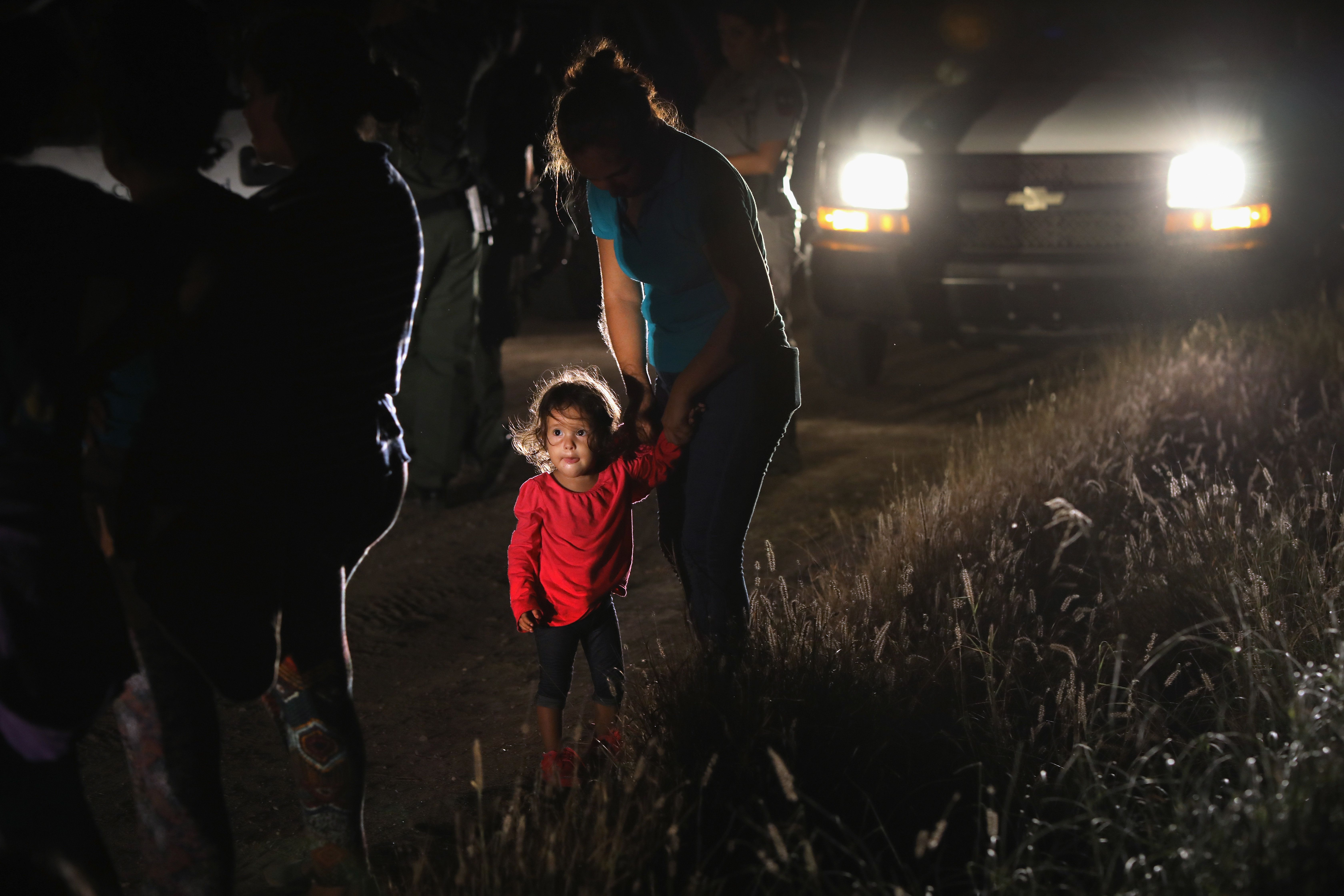 MCALLEN, TX - JUNE 12:  A two-year-old Honduran stands with her mother after being detained by U.S. Border Patrol agents near the U.S.-Mexico border on June 12, 2018 in McAllen, Texas. The asylum seekers had rafted across the Rio Grande from Mexico and were detained  before being sent to a Border Patrol processing center for possible separation. Customs and Border Protection (CBP) is executing the Trump administration's 'zero tolerance' policy towards undocumented immigrants. U.S. Attorney General Jeff Sessions also said that domestic and gang violence in immigrants' country of origin would no longer qualify them for political asylum status.  (Photo by John Moore/Getty Images)