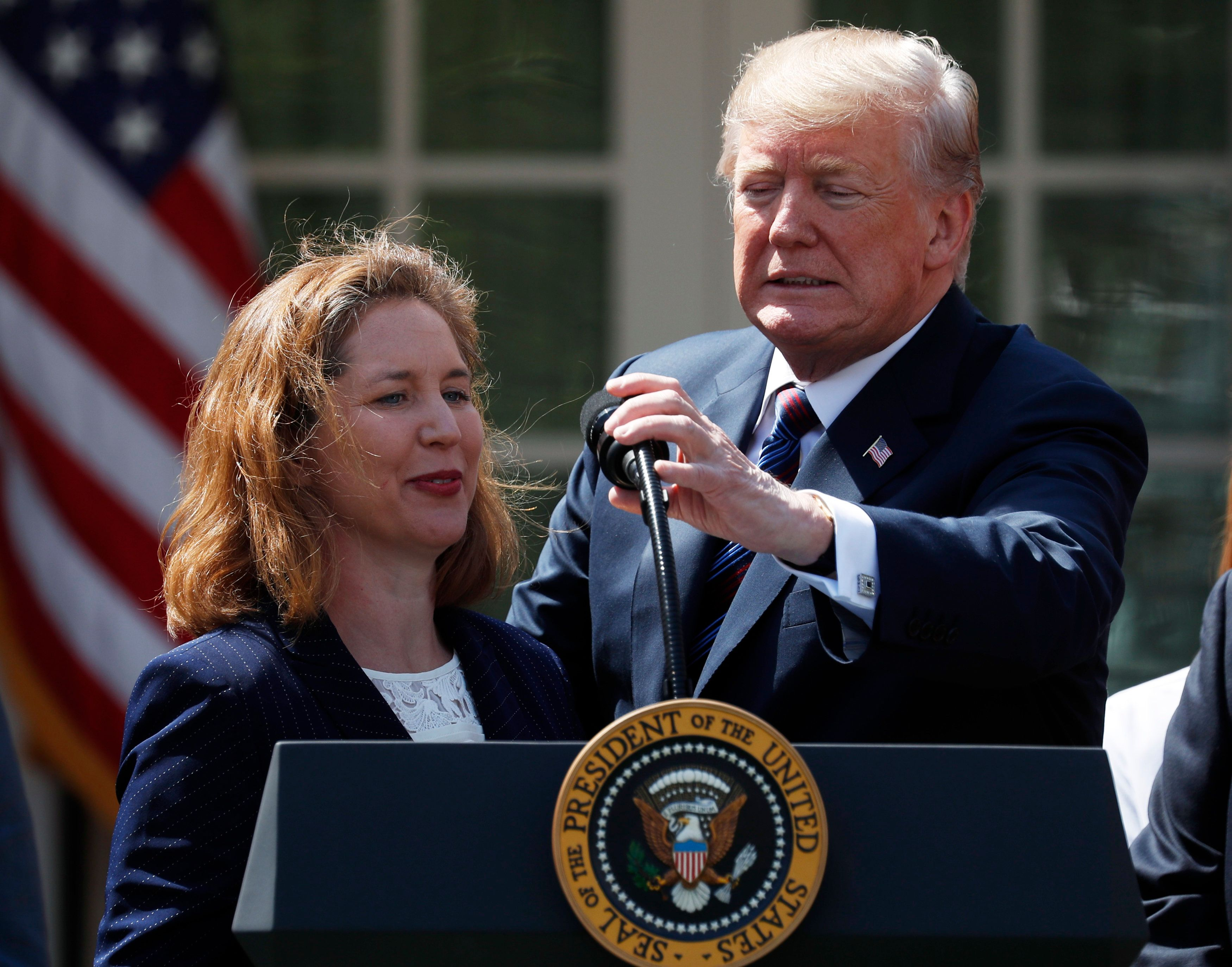 U.S. President Donald Trump adjusts the mic for Nicole Bergstrom of Smithcraft Signs of Avondale, Arizona while delivering remarks on tax cuts for American workers during an event in the White House Rose Garden in Washington, U.S., April 12, 2018. REUTERS/Kevin Lamarque