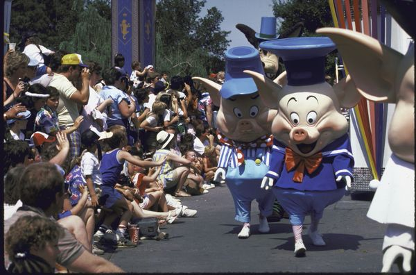Cast members parade past the crowd at Disney World.