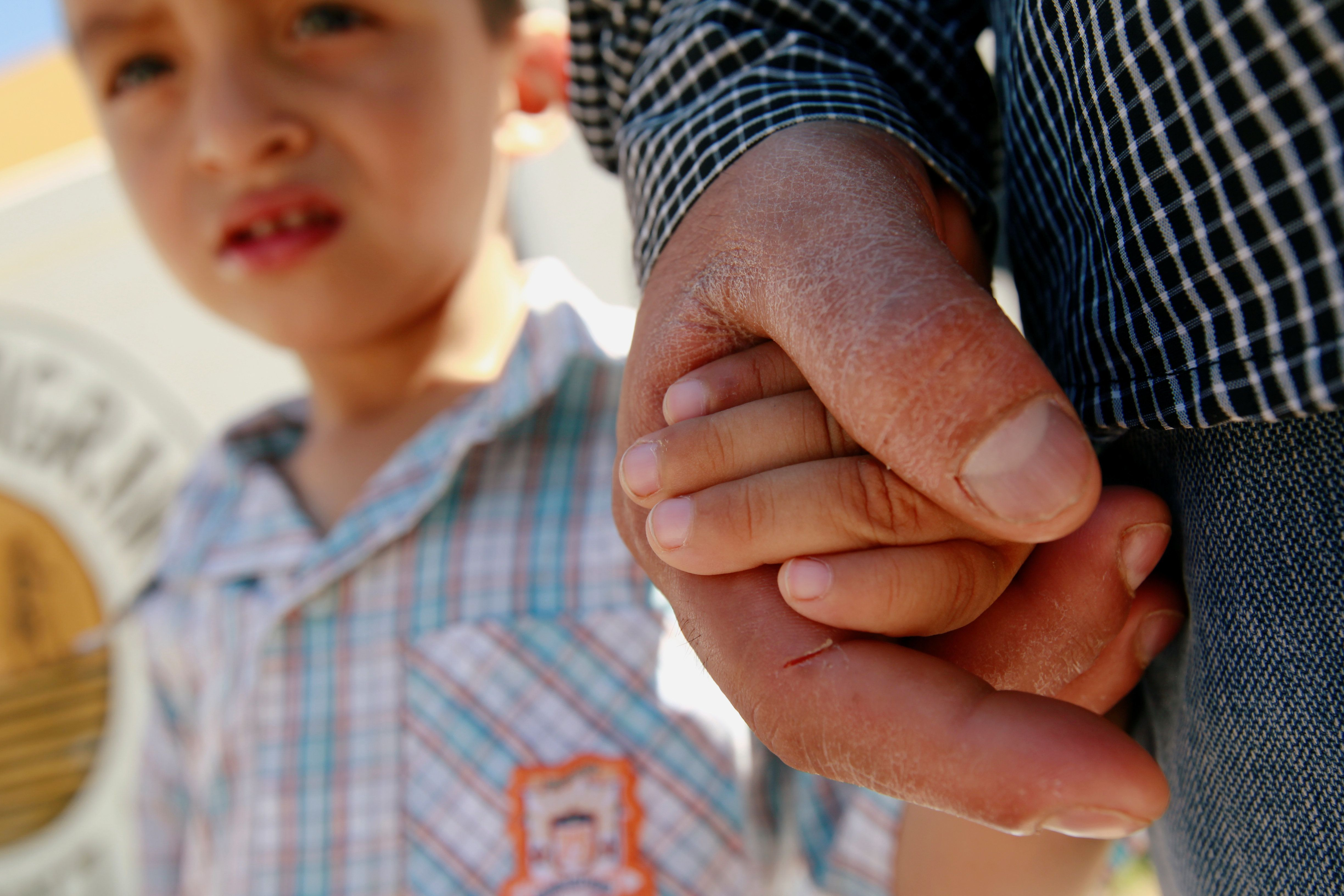Salvadoran migrant Epigmenio Centeno holds the hand of his three-year old son Steven Atonay outside the shelter House of the Migrant, after he has decided to stay with his children in Mexico due to U.S. President Donald Trump's child separation policy, in Ciudad Juarez, Mexico June 19, 2018. REUTERS/Jose Luis Gonzalez
