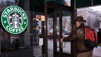 A customer pulls on the locked doors of a the Starbucks Coffee shop at 15th & K Streets in Washington, DC, closed for employee re-training on February 26, 2008. Starbucks coffee lovers were deprived of their caffeine fix for an agonizing three hours on February 26th as the firm closed its 7,100 shops across America to train staff to brew the perfect cup of joe. From Washington state to Washington, DC, 135,000 Starbucks employees went into training sessions at 5:30 pm to hone their craft and make the tastiest possible capuccino, espresso or latte. The Seattle, Washington-based company described it as an 'historic in-store education and training event' designed to 'energize partners and transform the customer experience.' Starbucks, which has been facing increasing competion lately, including from fast-food restaurant McDonald's, announced the layoff of 600 employees last week.   Another top competitor, Dunkin Donuts', seized on Starbucks' three-hour nationwide closure to offer a special deal on its coffees. 'Dunkin' Donuts wants to ensure that no coffee lover is denied a delicious espresso-based beverage,' the chain said in a statement.    AFP PHOTO/Paul J. Richards (Photo credit should read PAUL J. RICHARDS/AFP/Getty Images)