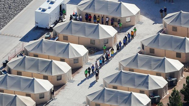 """Immigrant children now housed in a tent encampment under the new """"zero tolerance"""" policy by the Trump administration are shown walking in single file at the facility near the Mexican border in Tornillo, Texas, U.S. June 19, 2018.        REUTERS/Mike Blake"""