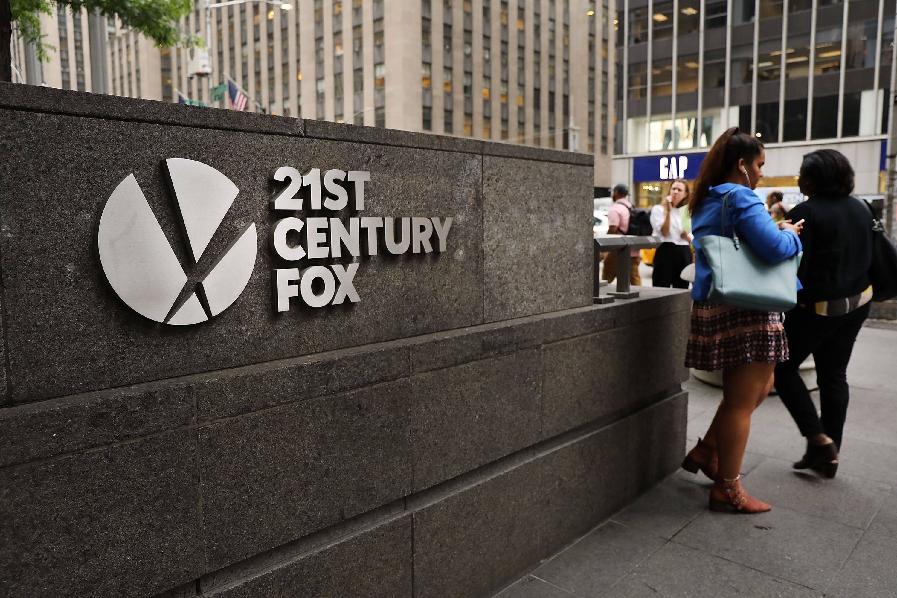 NEW YORK, NY - JUNE 13:  People walk by the headquarters of 21st Century Fox on June 13, 2018 in New York City. Comcast, the giant cable operator, on Wednesday officially made a $65 billion all-cash bid for the majority of Fox.  (Photo by Spencer Platt/Getty Images)