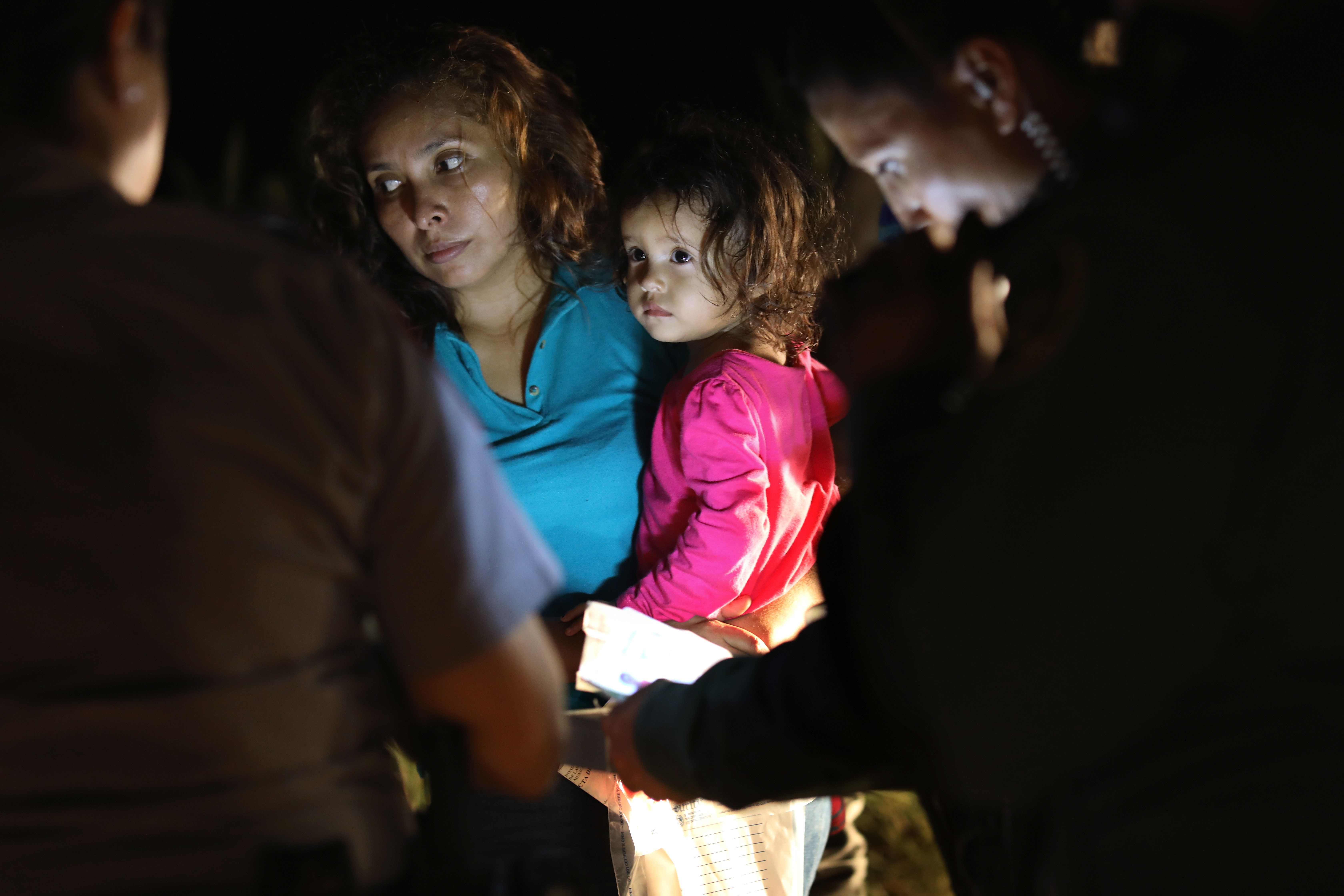 MCALLEN, TX - JUNE 12:  A Honduran mother holds her two-year-old as U.S. Border Patrol as agents review their papers near the U.S.-Mexico border on June 12, 2018 in McAllen, Texas. The asylum seekers had rafted across the Rio Grande from Mexico and were detained by U.S. Border Patrol agents before being sent to a processing center for possible separation. Customs and Border Protection (CBP) is executing the Trump administration's 'zero tolerance' policy towards undocumented immigrants. U.S. Attorney General Jeff Sessions also said that domestic and gang violence in immigrants' country of origin would no longer qualify them for political asylum status.  (Photo by John Moore/Getty Images)