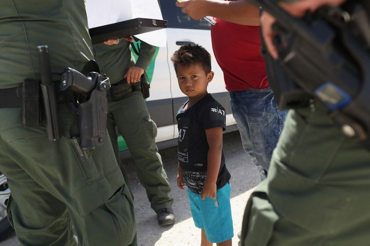 U.S. Border Patrol agents take into custody a father and son from Honduras near the U.S.-Mexico border on June 12, 2018, near Mission, Texas.