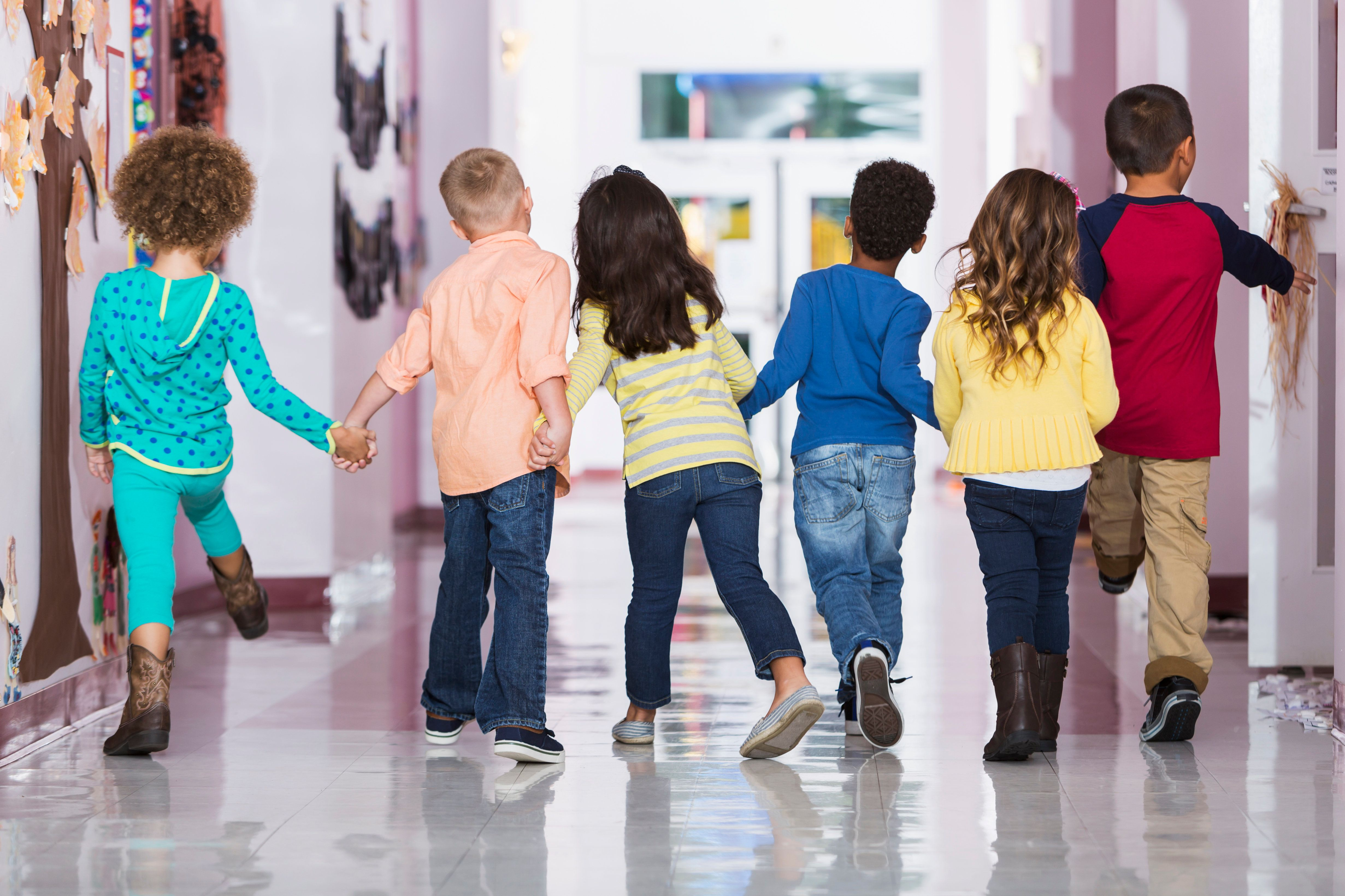 Rear view of a multi-ethnic group of six children holding hands, walking down a school hallway together.  They are in kindergarten or preschool 4 to 6 years old.