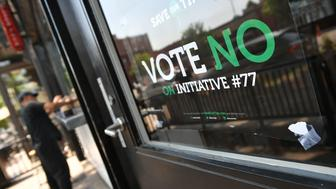 A man stands near a 'vote no on Initiative #77' sign on June 18, 2018 in Washington, DC. - Washington, DC's upcoming primary election includes a ballot measure called Initiative 77, a policy to gradually raise the minimum wage that tipped workers receive. (Photo by MANDEL NGAN / AFP)        (Photo credit should read MANDEL NGAN/AFP/Getty Images)
