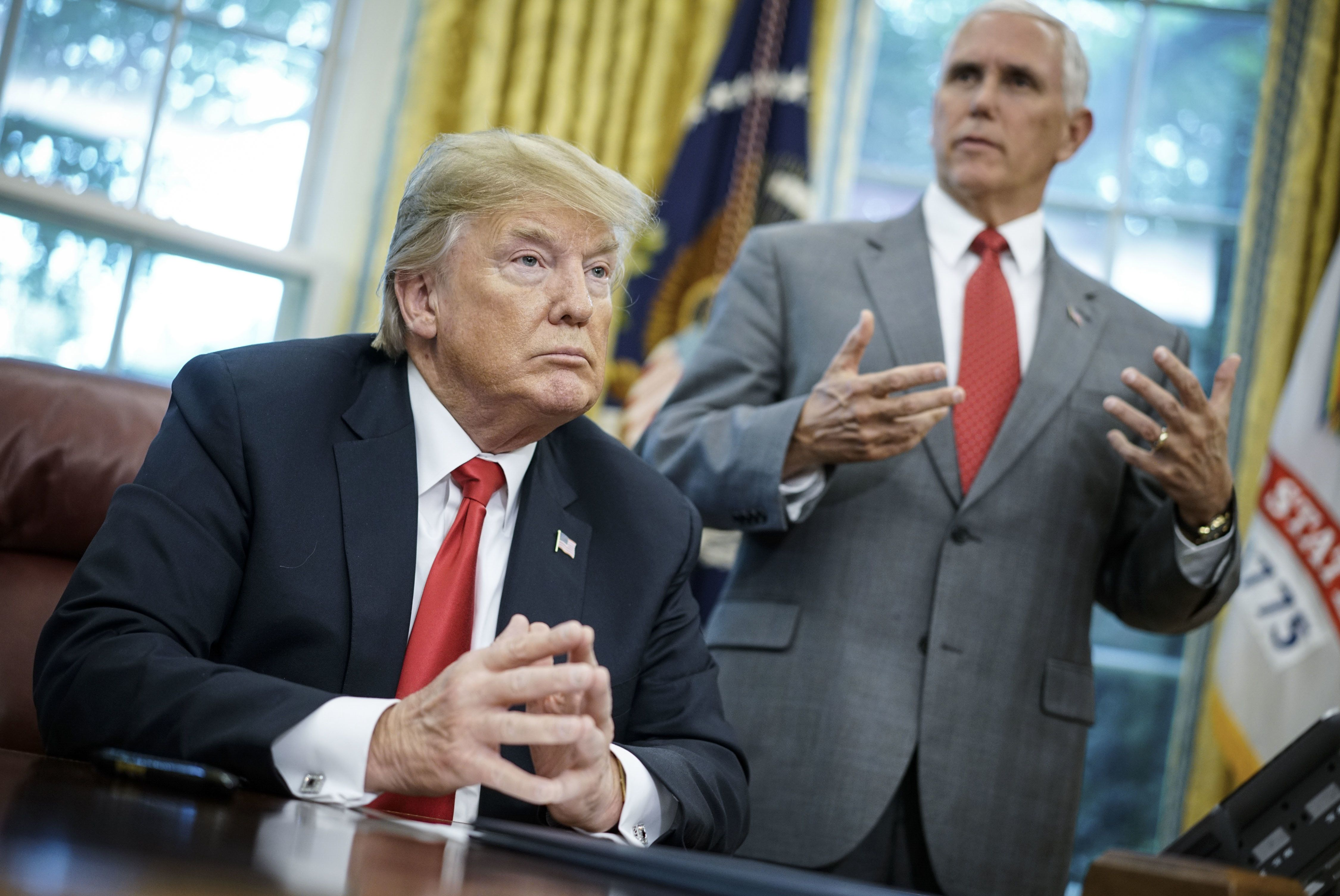 US Vice President Mike Pence speaks as US President Donald Trump looks on before signing an executive order on immigration in the Oval Office of the White House on June 20, 2018 in Washington, DC. - US President Donald Trump on Wednesday signed an executive order aimed at putting an end to the controversial separation of migrant families at the border, reversing a harsh practice that had earned international scorn.'It's about keeping families together,' Trump said at the signing ceremony. 'I did not like the sight of families being separated,' he added. (Photo by Mandel Ngan / AFP)        (Photo credit should read MANDEL NGAN/AFP/Getty Images)