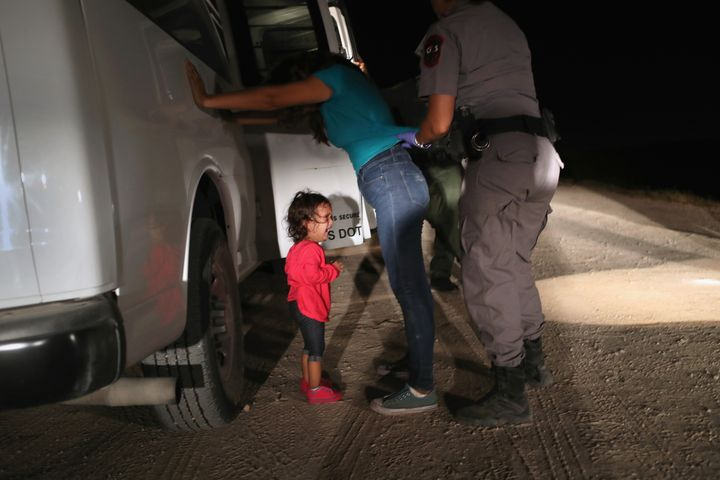 A 2-year-old Honduran girl cries as a Border Patrol agent searches her mother near the border between the U.S. and Mexico.