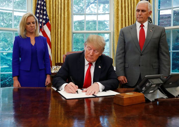President Donald Trump signs an executive order on immigration policy on June 20, 2018, as Department of Homeland Security Se