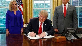 U.S. President Donald Trump signs an executive order on immigration policy with DHS Secretary Kirstjen Nielsen and Vice President Mike Pence at his sides in the Oval Office at the White House in Washington, U.S., June 20, 2018.  REUTERS/Leah Millis