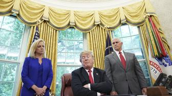 Watched by Homeland Security Secretary Kirstjen Nielsen (L) and Vice President Mike Pence, US President Donald Trump signs an executive order on immigration in the Oval Office of the White House on June 20, 2018 in Washington, DC. - US President Donald Trump on Wednesday signed an executive order aimed at putting an end to the controversial separation of migrant families at the border, reversing a harsh practice that had earned international scorn.'It's about keeping families together,' Trump said at the signing ceremony. 'I did not like the sight of families being separated,' he added. (Photo by Mandel Ngan / AFP)        (Photo credit should read MANDEL NGAN/AFP/Getty Images)