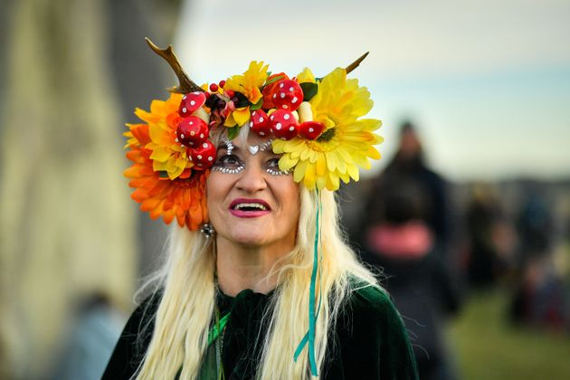 A woman wears a colourful headdress as she celebrates the dawn of the longest day in the