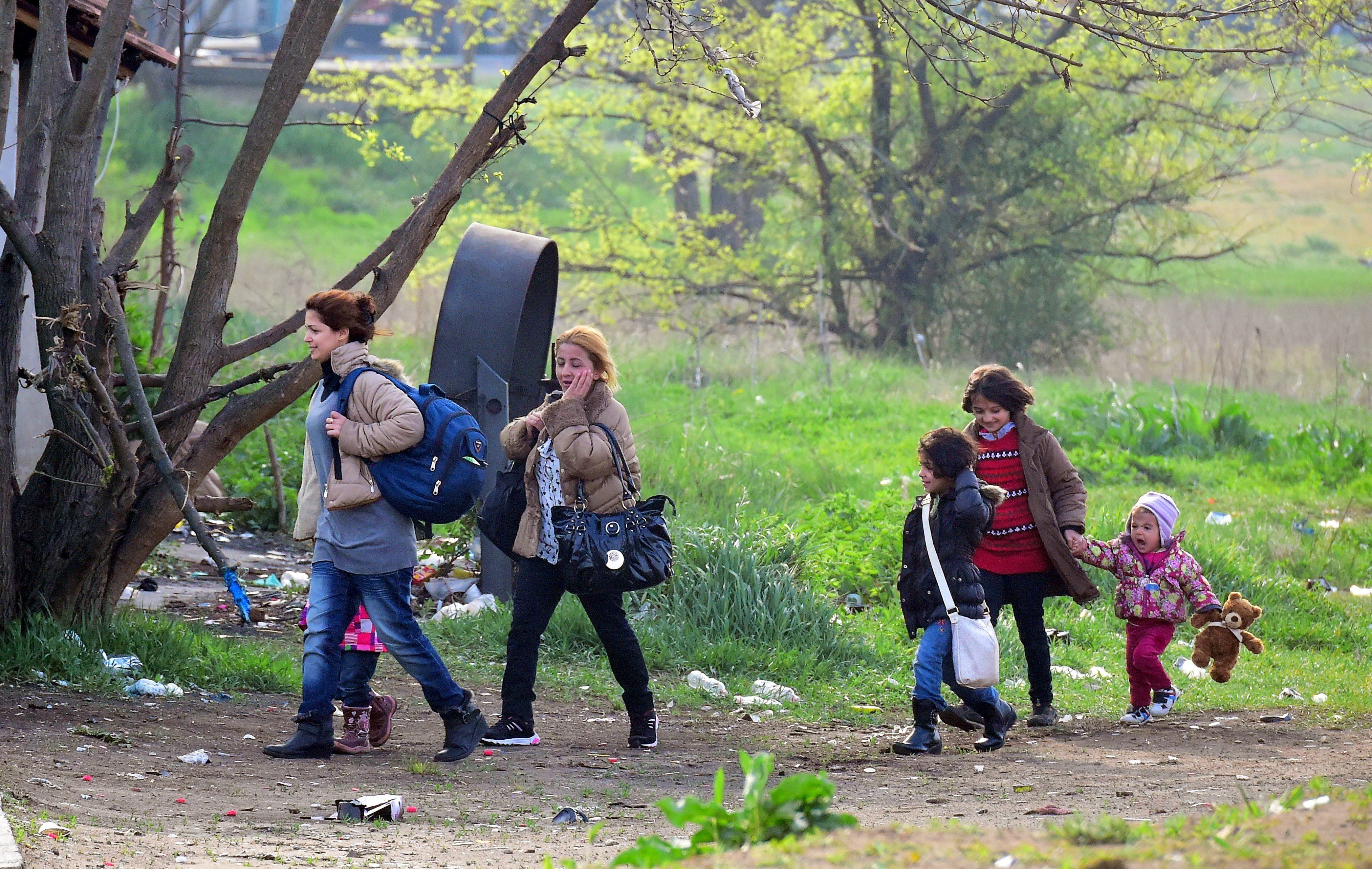 A Syrian family carry their belongings through the forest near the Hungarian border fence at the Tompa border station transit zone on April 6, 2017 as the Hungarian Interior Minister Sandor Pinter (not pictured) presented the camp to the media.   The migrant transit complex on the Hungarian side of the border has been expanded to become one of two new detention centers for asylum seekers in the Hungarian transit zone and contains shipping containers that are used to automatically detain migrants in the transit zone while their claims are investigated.   / AFP PHOTO / ATTILA KISBENEDEK        (Photo credit should read ATTILA KISBENEDEK/AFP/Getty Images)