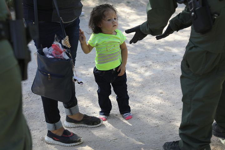 U.S. Border Patrol agents take Central American asylum seekers into custody on June 12 near McAllen, Texas. The immigrant fam