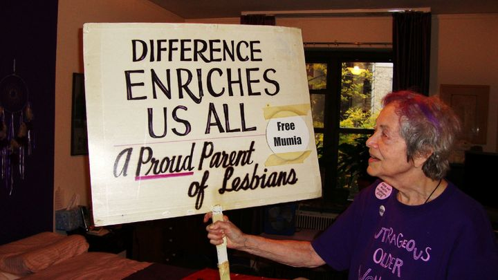 Frances Goldin shows the other side of her sign.
