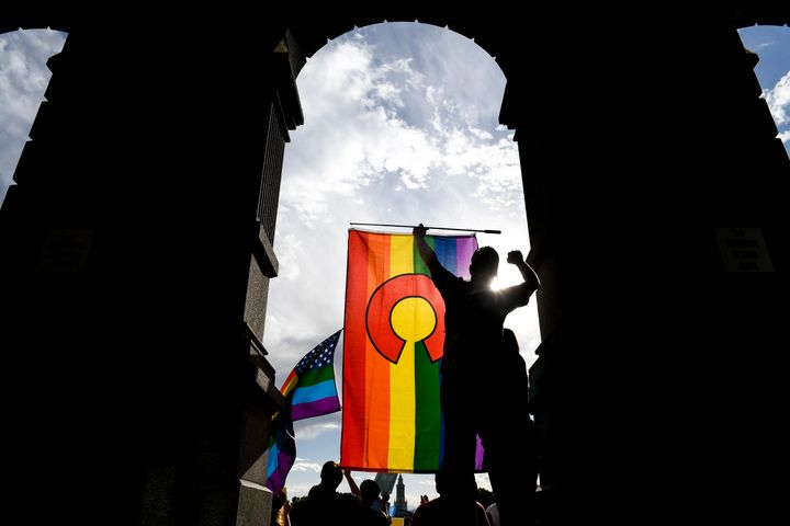 Aprotester holds a Colorado pride flag during a rallyat the Colorado State Capitol after the Supreme Court ruled
