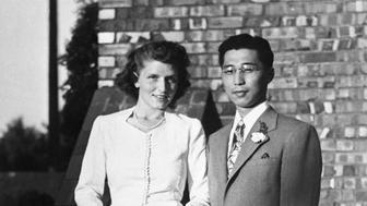 Gordon K. Hirabayashi, a U.S. born Japanese-American, is shown with his bride, Esther Schmoe of of Seattle, Washington, after their Quaker wedding ceremony in Spokane, Washington.  Their romance began at the University of Washington where both were students before U.S. entry into World War II.  Hirabayashi made history as one of the Japanese Americans that defied the U.S. Government's order of evacuation to concentration camps in 1942.  As a result of his conscioutious objection, he was arrested, convicted and imprisoned.