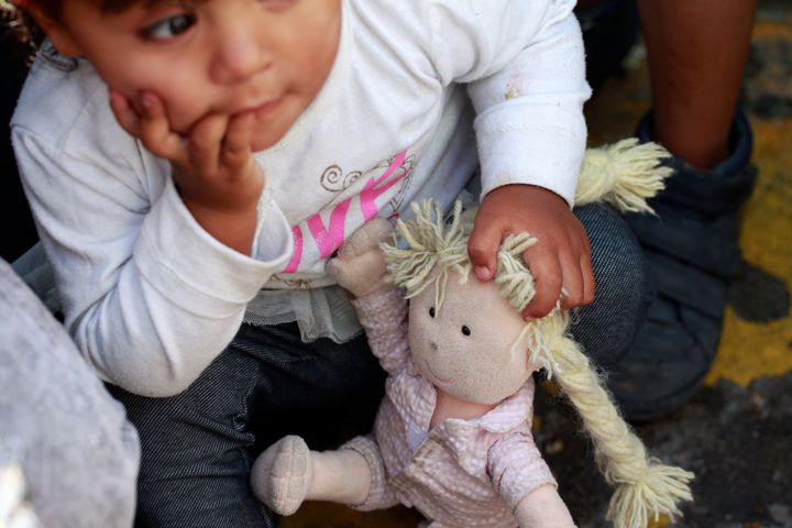 Agirl from Mexico waits with members of her family, fleeing from violence, to apply for asylum in the U.S., at Paso del